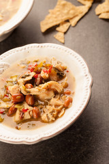 White chicken chili with red peppers, chicken, and beans in white bowl with corn tortilla chips angled shot