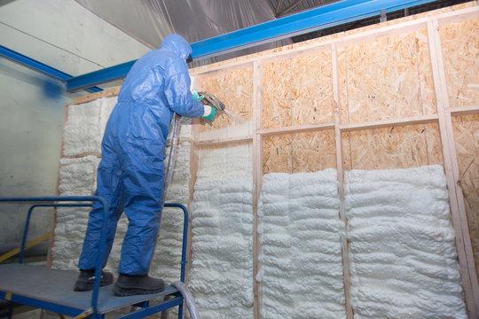 A man in a blue suit is applying foam on a wooden wall