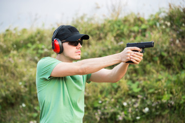 Special force policeman soldier from military army camp wants to shoot the enemy with gun glock desert eagle pistol and full body equipment and gun holder want to kill and aim at distant target