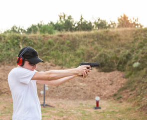 Handsome young policeman agent aiming and shooting at a target with a pistol glock desert eagle gun wearing black hat and white shirt in nature ambient firing firearms bullets in the air training