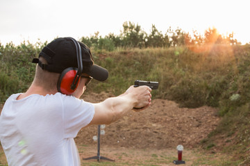 Special force training military camp secret service agent handsome young blonde guy strong fire shoot at the target with bullets from gun glock pistol desert eagle aim to kill enemy target in distance
