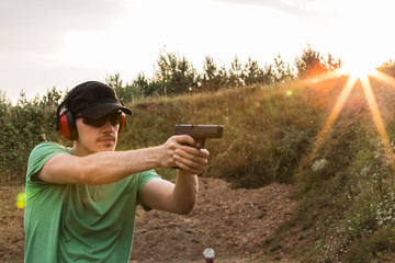 Profile of a young handsome policeman during training in the battlefield outside of the city ready to take criminals and shooting with the gun glock pistol at the target professional in the nature