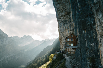 Wildkirchli mountain inn in the Switzerland alps overlooking a forest on a sunny afternoon day with clouds