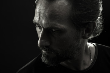 Monochrome portrait of strong man turnig face to left side. Close up view of mature wrinkled male showing emotion of frustration and troubleness. Wall mural