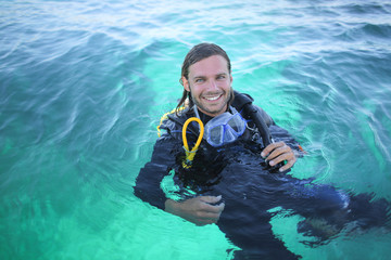 Handsome guy in the sea, carrying scuba diving equipment