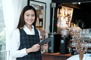 Young asian woman using tablet at cafe background, food and drink concept