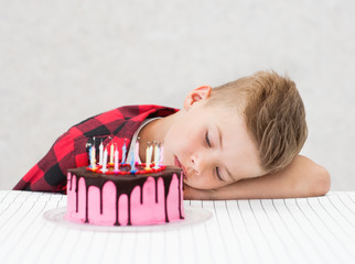 Sad boy lying near cake with extinct candles Wall mural