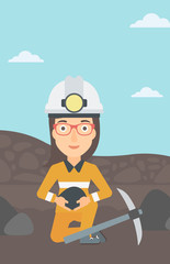 A woman sitting with coal in hands and a pickaxe on the background of coal mine vector flat design illustration. Vertical layout.