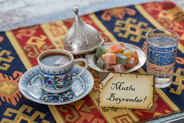 Happy eid text in turkish on greeting card with turkish coffee, delights on traditional tablecloth