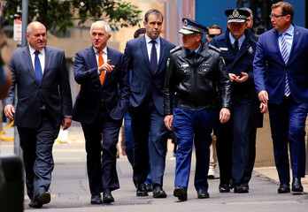 Australian Prime Minister Malcolm Turnbull walks with officials along a street before holding a media conference announcing Australia's national security plan to protect public places in central Sydney, Australia