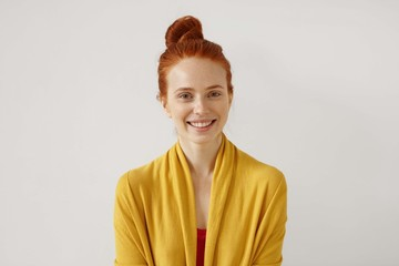 Studio shot of amazing gorgeous young red-haired European female model with healthy freckled skin and no make up posing at white wall, grinning broadly, having happy expression on her pretty face