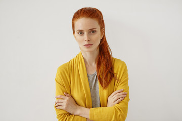 Young Caucasian woman with red hair tied in pony tail, having appealing appearance with freckles, looking with serious expression while keeping her hands crossed, isolated over white background Wall mural