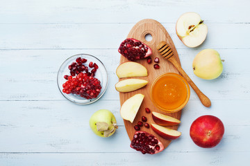 Honey, apple slices and pomegranate serve on wooden kitchen board overhead view. Table set with traditional food for Jewish New Year Holiday, Rosh Hashana.