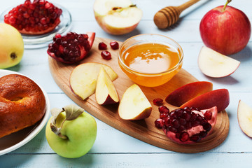Honey, apple slices, pomegranate and hala serve on kitchen board. Table set with traditional food for Jewish New Year Holiday, Rosh Hashana.