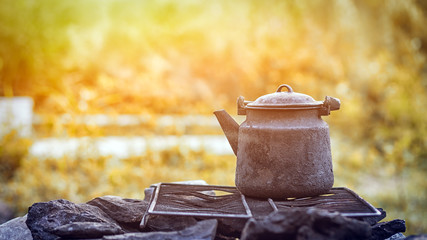 An old cast-iron burnt kettle stands on a black rimmed grate on the rocks and warms the water on the nature in the mountains on a summer day. Still life of things on a mountain theme