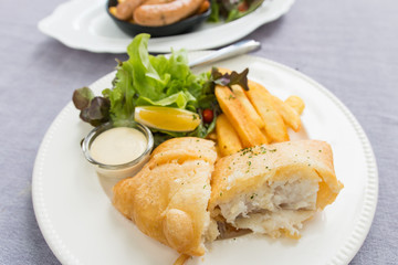 fish and chips served on a white plate