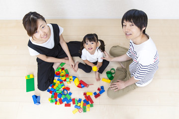 両親と玩具で遊ぶ幼い女の子の俯瞰
