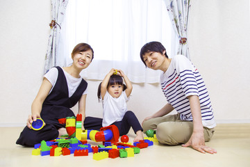 両親と玩具で遊ぶ幼い女の子