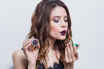 Beautiful, sexy brunette girl with professional make up, bright lips advertises cosmetics, blowing glitter powder, eye shadow, blue dress, close-up, white background