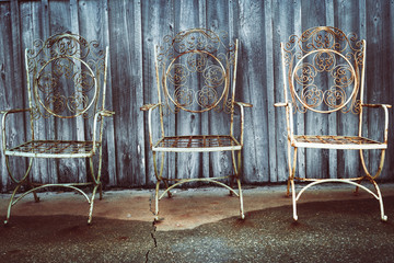 vintage iron chairs in front of weathered building
