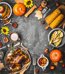 Thanksgiving dinner background with roasted turkey , sauce , pumpkin and dishes of  autumn vegetables on rustic background, top view, frame