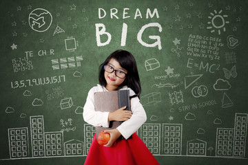 Child with Dream Big text on chalkboard
