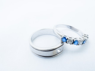 white diamond and blue gemstones on wedding rings with white background and copy space