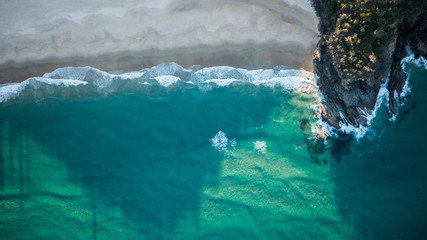 Drone shot of a rocky headland at sunset with small breaking waves in emerald blue water.