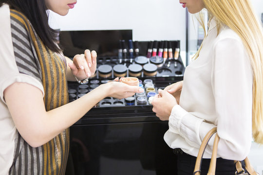Young pretty woman and beauty consultant in shop