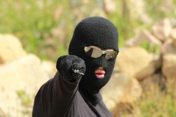Man aggressor with balaclava hold knife/ Man aggressor in black clothes with balaclava hold knife.