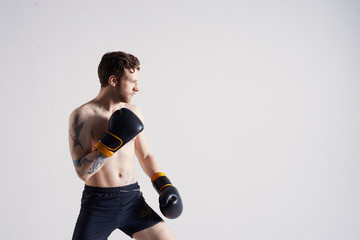 Studio portrait of attractive young European fighter with muscular athletic body wearing shorts and boxing gloves, training, standing at blank grey wall with copy space for your text or information
