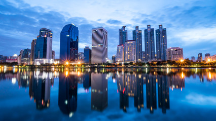 Night light cityscape view with modern building in the park beside lake at Bangkok, Thailand (Blue color tone)