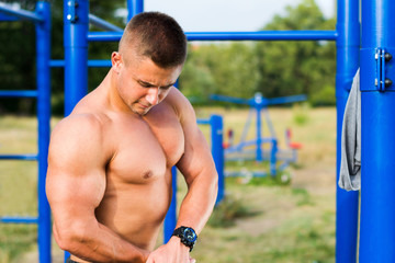 Man showing muscles in street workout park