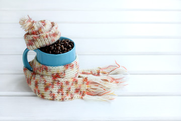 Winter warming drink/ Natural grain coffee in a blue mug that is dressed in a scarf and hat