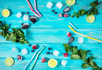 Foto op Plexiglas Draw fresh berries, lime, mint and ice cubes on blue wood background top view.
