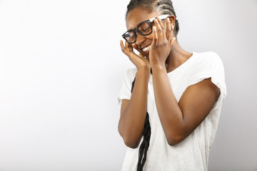 Happy and smiling african woman with glasses in white shirt