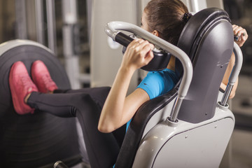 Young fit woman leg press in a fitness center. Portrait of fitness girl in the gym, lifestyle concept.