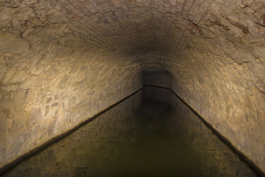 Flooded round sewer tunnel is reflecting in water