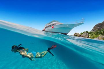 Small safari boat with snorkeling woman underwater.