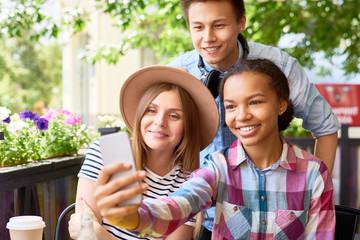 Teenage Friends Taking Selfie in Cafe