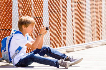 Young boy sitting with a digital camera and taking pictures in the street