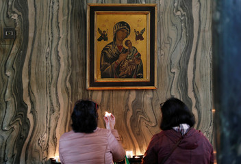 A woman holds a candle to a picture of the Virgin Mary holding Jesus, before mass at Westminster Cathedral in London