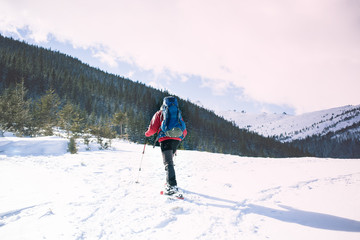 mountaineer with a backpack goes along the route.