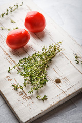 Thyme branches and two tomatoes on a light background