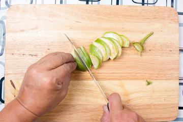 Hand cutting Thai Brinjal on wooden broad
