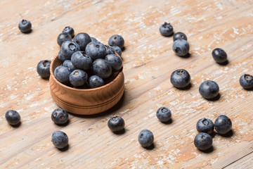 Black ripe berries lie on a wooden saucer and scattered on an old board