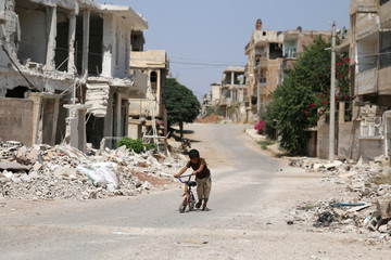 A boy holds a bike along a damaged street in a rebel-held part of the southern city of Deraa