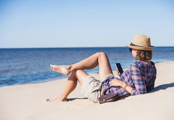Young woman lying on a beach with smart phone. Technology and travel concept. People using mobile devices to stay connected from remote parts of the world