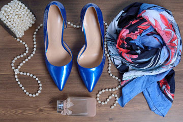 Women's accessories (scarf, blue lacquered shoes, perfume and beads on a wooden background