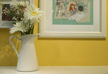 White flower vase on white table with white picture frames on the yellow wall